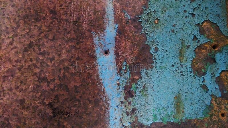 极端特写镜头铁锈由在被绘的长期白色的阴沉的坏天气表示纹理镀锌了钢波纹状的板料篱芭 免版税图库摄影