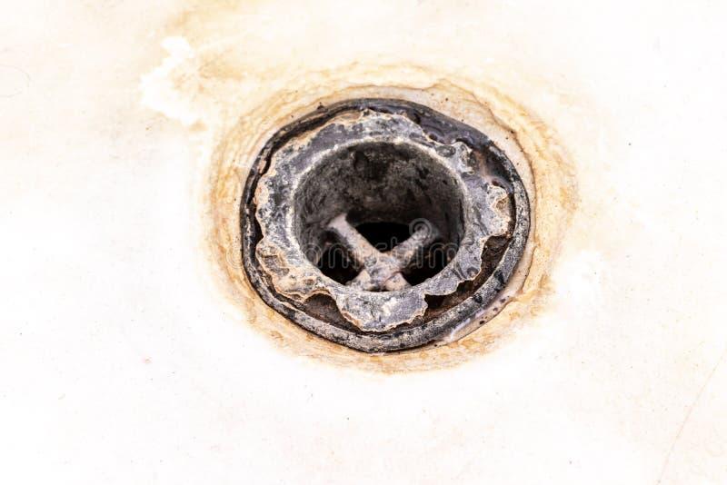 极端肮脏的浴流失滤网,用limescale或石灰按比例提高和铁锈关闭报道的孔,清洗钙化和生锈 库存图片