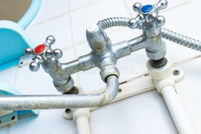 极端需要清洗肮脏的水龙头、老龙头有limescale的和铁锈在卫生间,阵雨明三联式浴缸水嘴钙化的细节  库存照片