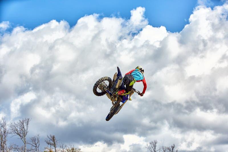 极限运动,摩托车跳跃 摩托车骑士做一个极端跃迁反对天空 库存图片