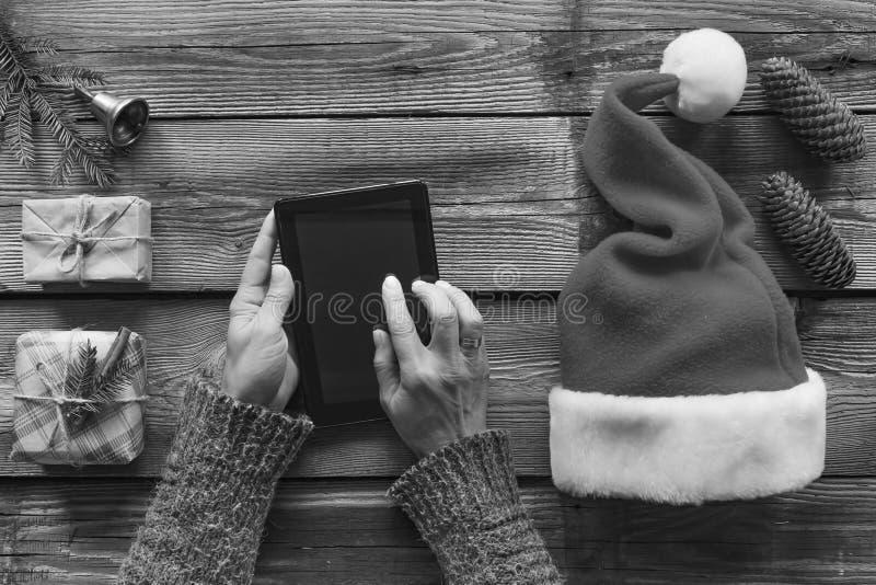 构想:圣诞节礼物的准备 一个人在他的手上拿着一台片剂个人计算机并且包装圣诞节礼物 免版税库存照片