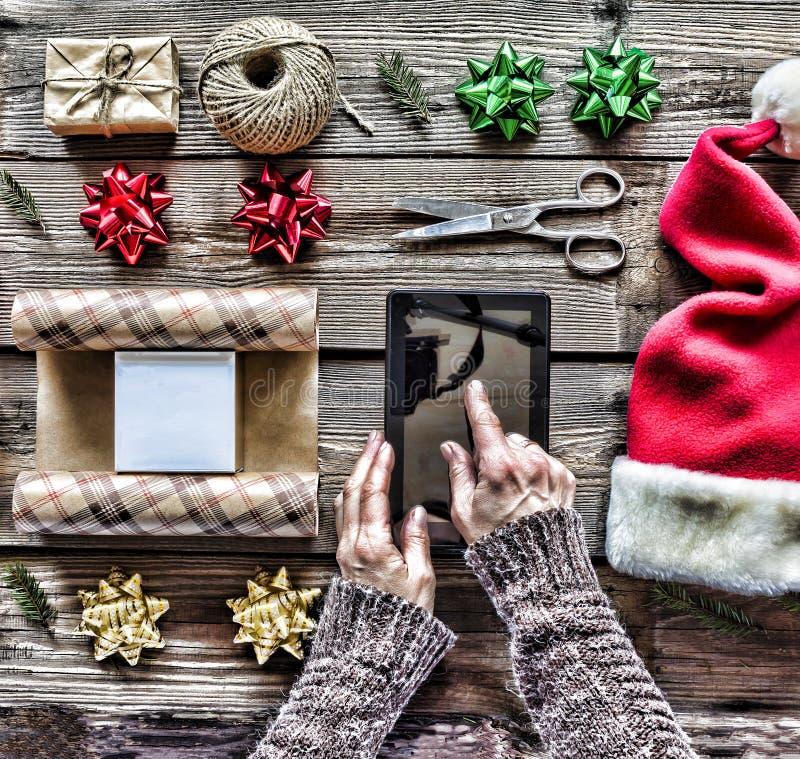 构想:圣诞节礼物的准备 一个人在他的手上拿着一台片剂个人计算机并且包装圣诞节礼物 库存照片