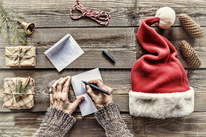 构想:圣诞节 做圣诞节礼物 一个人给家庭和朋友写信件贺卡 免版税库存图片