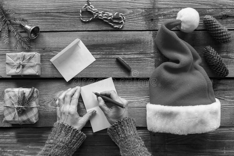 构想:圣诞节 做圣诞节礼物 一个人给家庭和朋友写信件贺卡 免版税库存照片