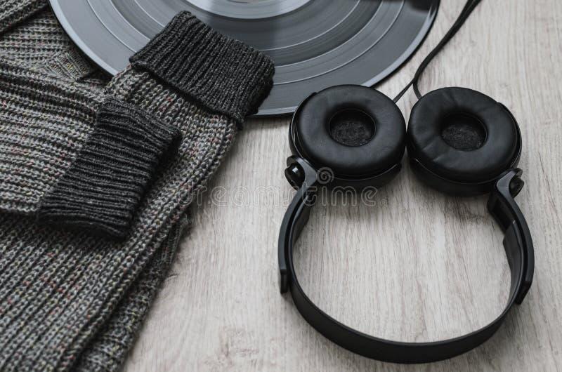 构成、羊毛运动衫黑色耳机和一个大唱片 免版税库存图片
