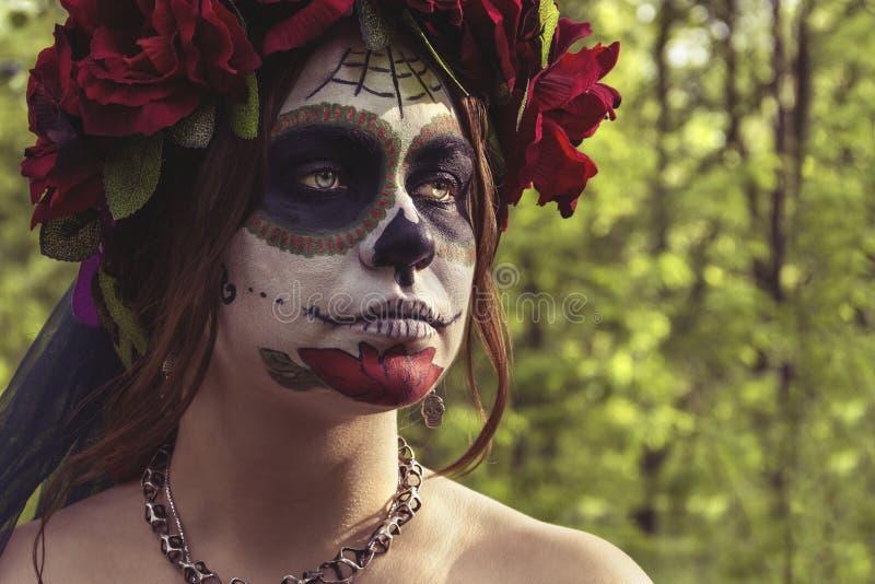 构成传统墨西哥人Calavera头骨的卡特里娜美女在秋天森林里,红色花花圈的  天  免版税库存图片