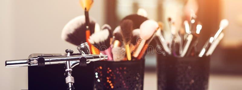 构成刷子,关闭 构成气刷和其他工具在桌上 构成产品集 化妆用品和刷子在艺术家workp 免版税库存照片