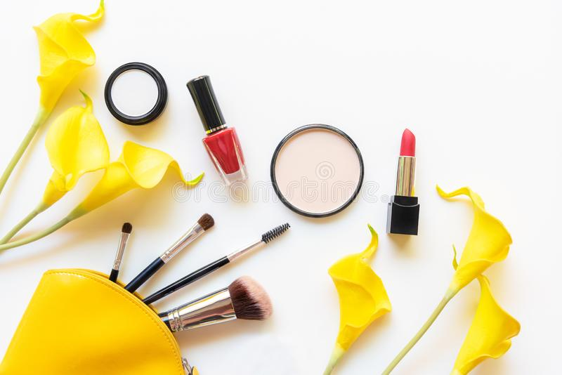 构成化妆用品工具和秀丽化妆用品礼物、产品和面部化妆用品包裹唇膏有黄色花的在白色b 免版税图库摄影