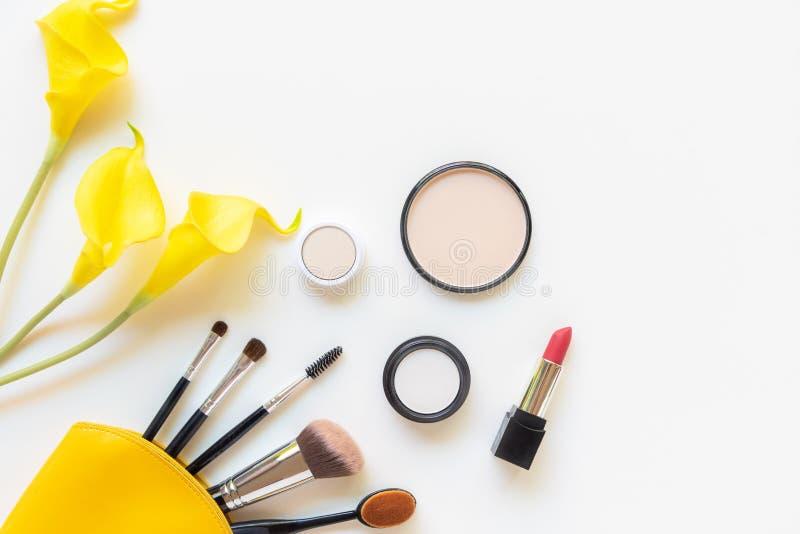 构成化妆用品工具和秀丽化妆用品礼物、产品和面部化妆用品包裹唇膏有黄色花的在白色b 免版税库存照片