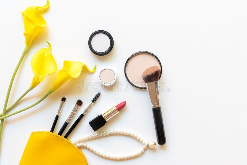构成化妆用品工具和秀丽化妆用品礼物、产品和面部化妆用品包裹唇膏有黄色花的在白色b 库存图片