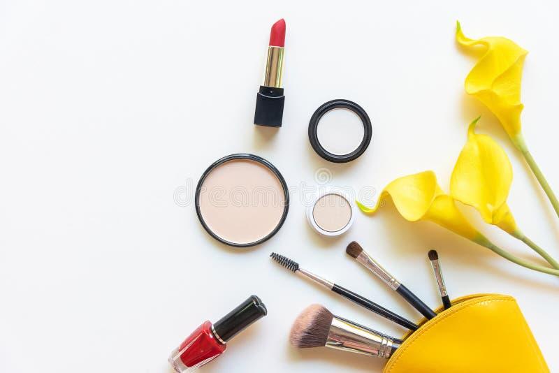 构成化妆用品工具和秀丽化妆用品礼物、产品和面部化妆用品包裹唇膏有黄色花的在白色b 免版税库存图片