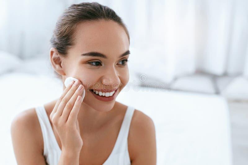 构成去除 与化妆垫的女孩清洗的面孔皮肤 图库摄影
