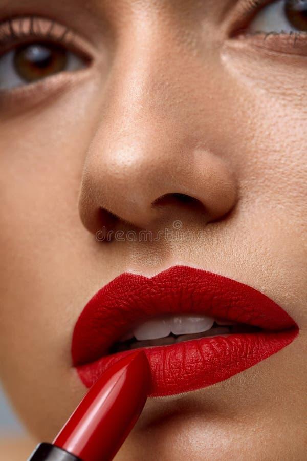 构成和化妆用品 与投入唇膏的红色嘴唇的妇女面孔 免版税图库摄影