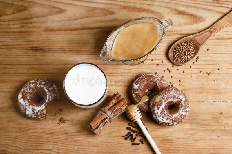 构成姜饼、牛奶和蜂蜜和香料-桂香,香菜,丁香,充塞了在木背景的姜饼,上面 库存照片
