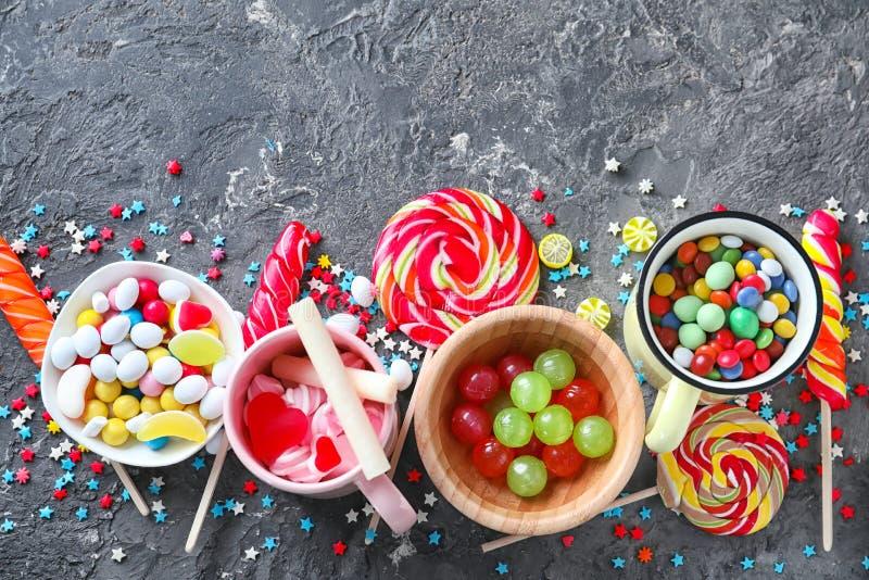 构成用五颜六色的糖果、棒棒糖和蛋白软糖在灰色织地不很细背景 库存照片