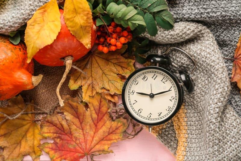 构成用南瓜、闹钟、温暖的格子花呢披肩和秋叶在颜色背景 库存照片