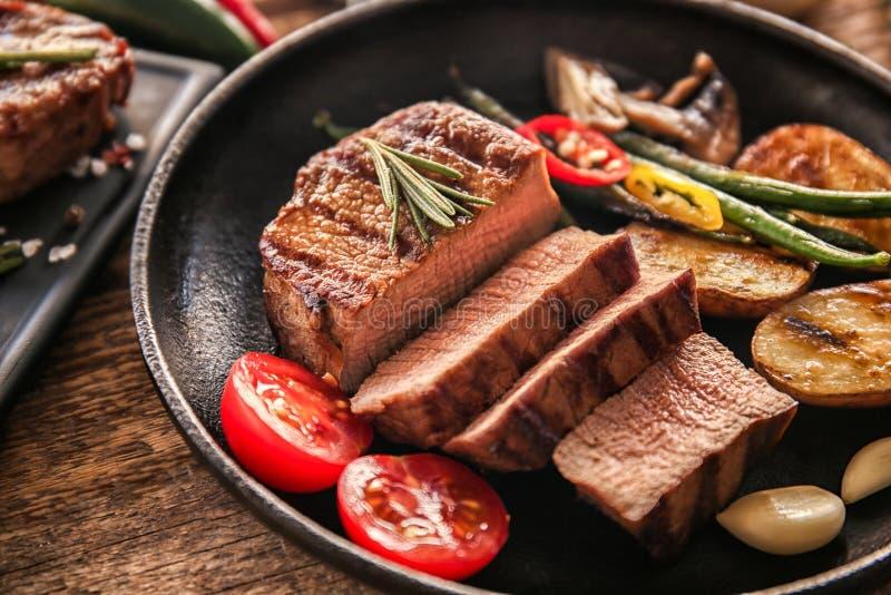 构成用在煎锅的可口牛排在桌上 图库摄影