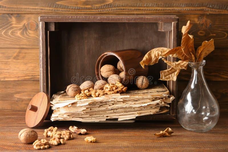 构成用核桃、旧书和花瓶有干燥叶子的在木桌上 图库摄影