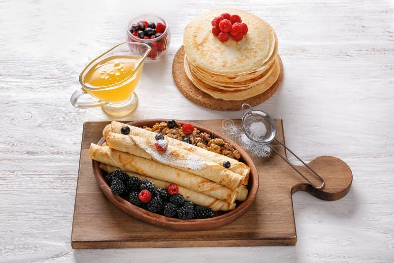 构成用滚动的稀薄的薄煎饼、蜂蜜和莓果在桌上 库存图片