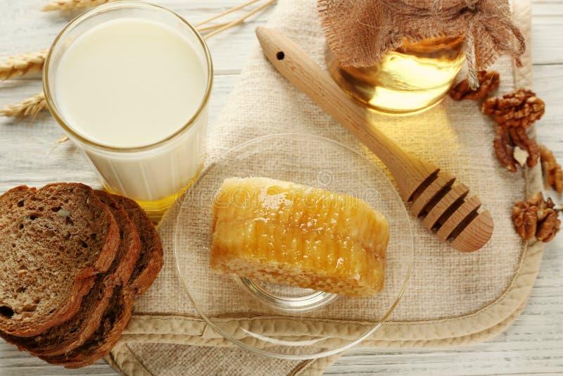 构成用牛奶、蜂蜜、面包和蜂窝 免版税库存图片