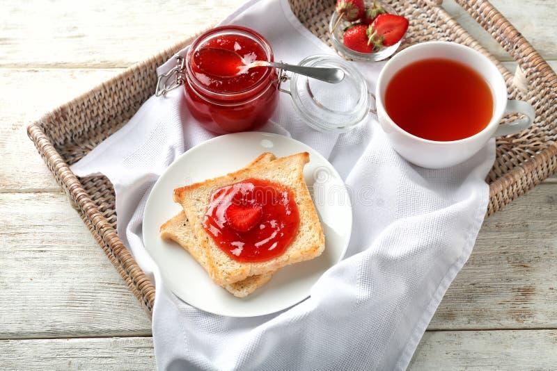 构成用草莓酱,在木桌上的茶和多士 免版税库存照片