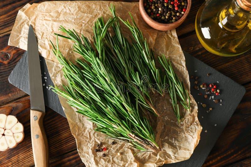 构成用迷迭香、油、胡椒、大蒜和刀子在木桌上 免版税库存图片