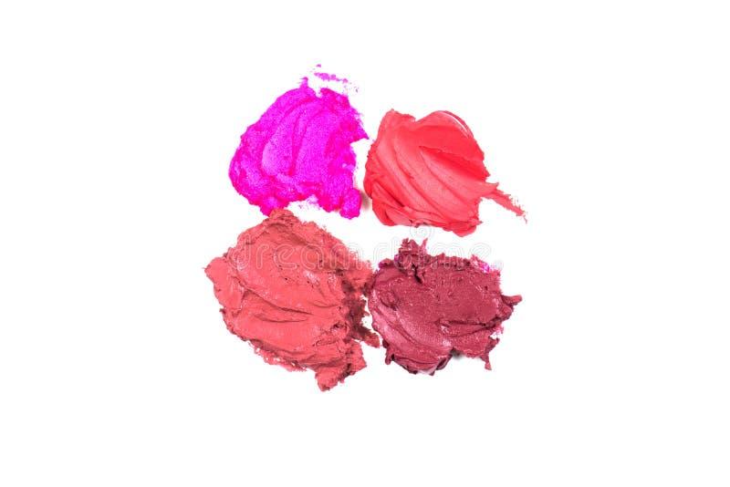 构成的乳脂状的五颜六色的唇膏 在白色背景的污迹 在白色背景和红色纹理隔绝的桃红色 免版税库存照片