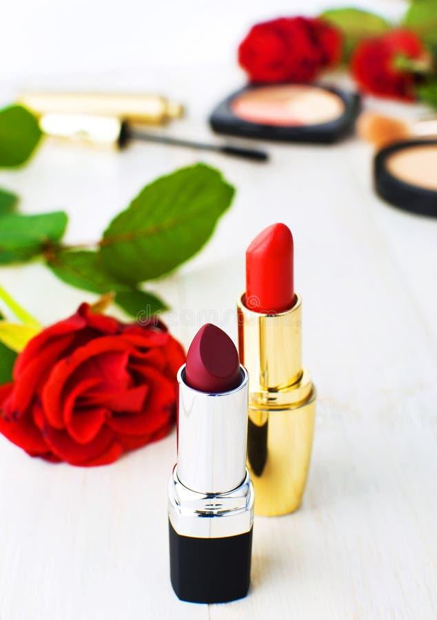 构成的各种各样的化妆产品与在白色木背景的英国兰开斯特家族族徽与拷贝空间 构成辅助部件红色唇膏 库存图片