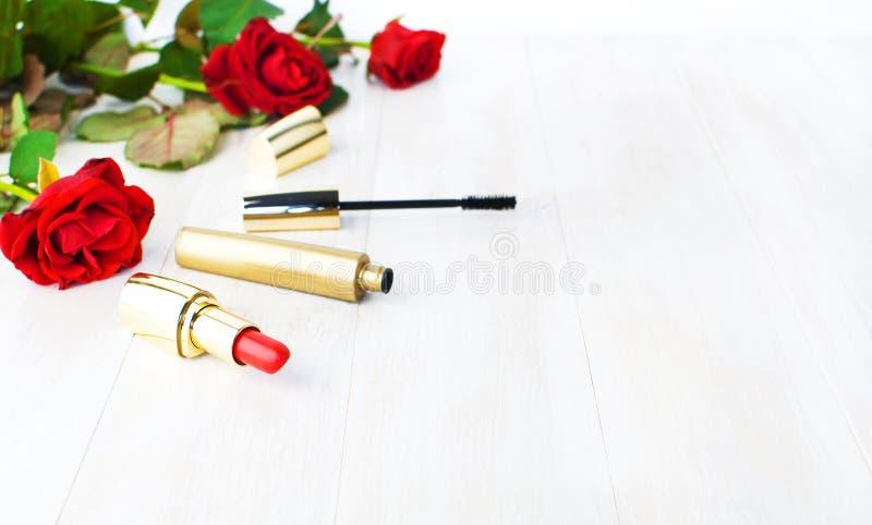 构成的各种各样的化妆产品与在白色木背景的英国兰开斯特家族族徽与拷贝空间 构成辅助部件红色唇膏 免版税图库摄影