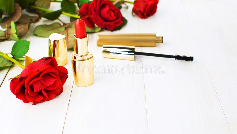 构成的各种各样的化妆产品与在白色木背景的英国兰开斯特家族族徽与拷贝空间 构成辅助部件红色唇膏 库存照片
