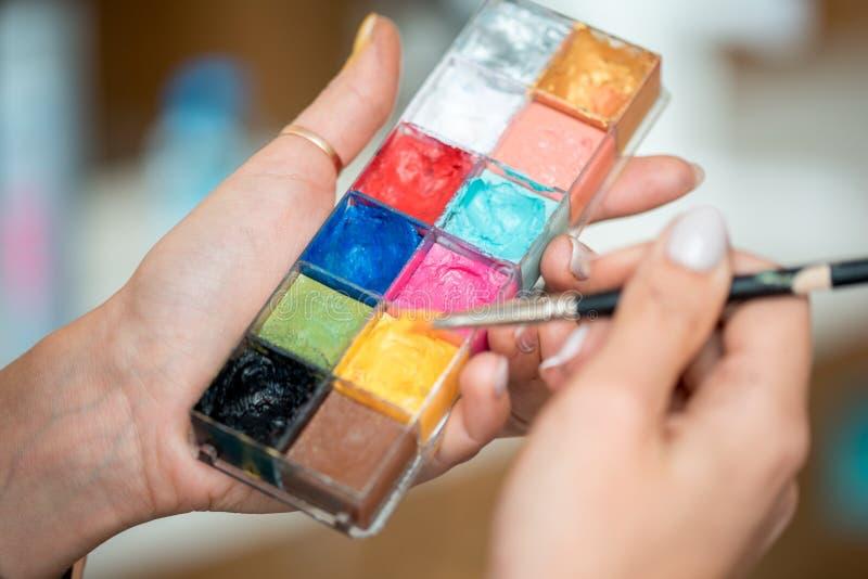 构成调色板?在面孔和人体艺术的化妆师明亮的颜色的手上 免版税库存图片