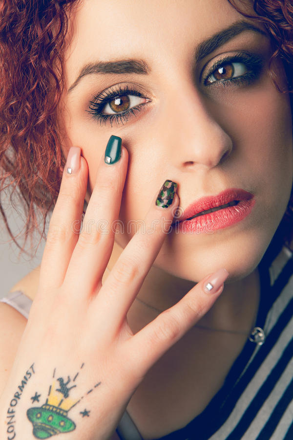 构成面孔和手钉子少妇 遵奉者纹身花刺 库存照片