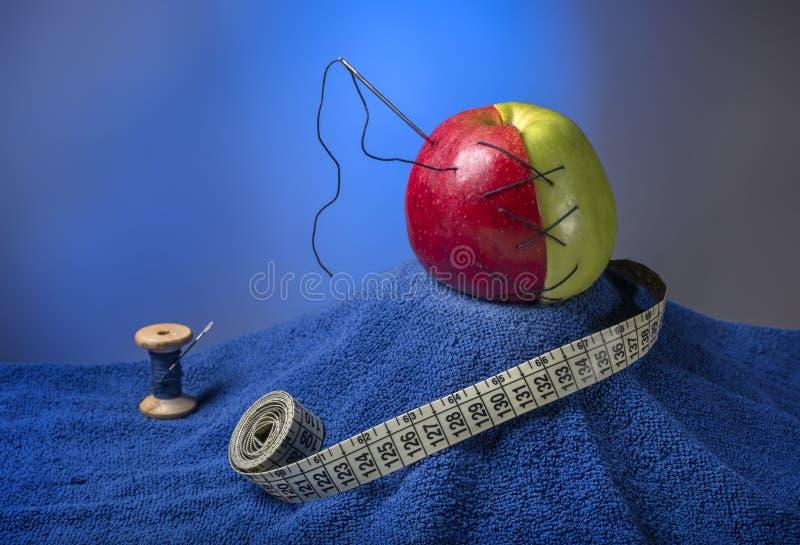构成:与针的绿色红色在一块蓝色毛巾的苹果和螺纹 在它附近螺纹和厘米蓝色卷缝合的 免版税库存图片