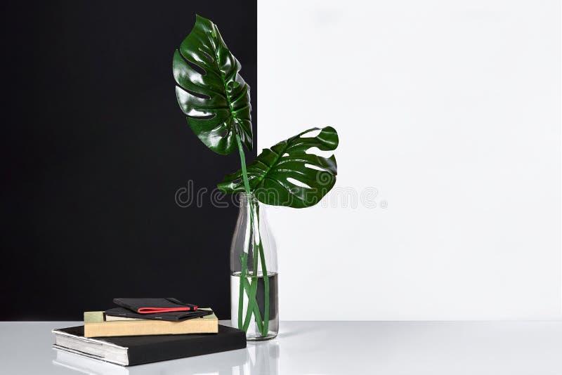 构成 绿色在瓶离开与一个书和笔记薄笔记的在白色和黑背景 正面图,拷贝 免版税库存照片