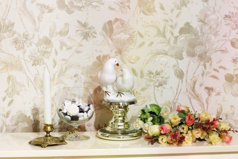构成 花、两只鸽子烛台和小雕象  免版税库存照片