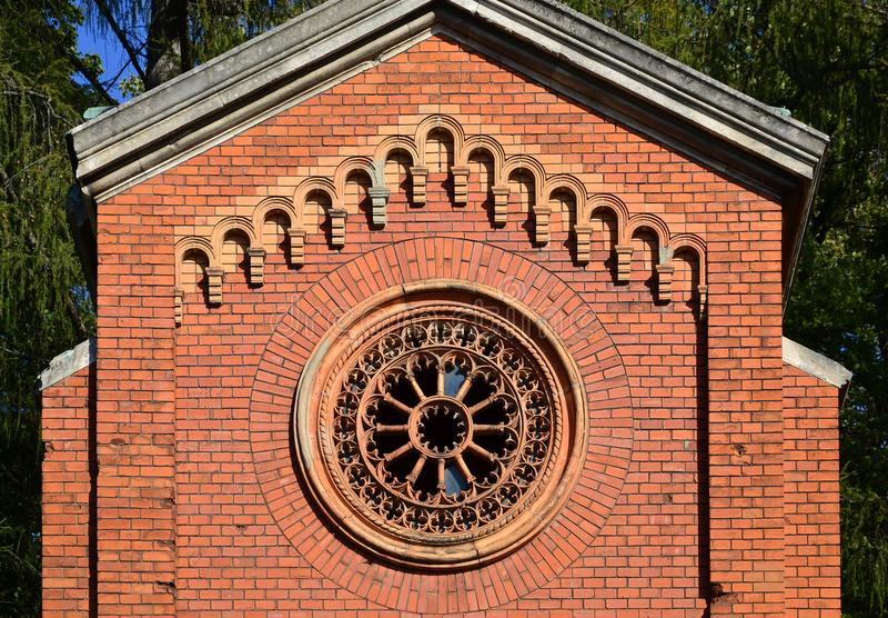 构造古老砖土窖的前面部分有一个回合被仿造的被雕刻的窗口的在cemeter 免版税库存照片
