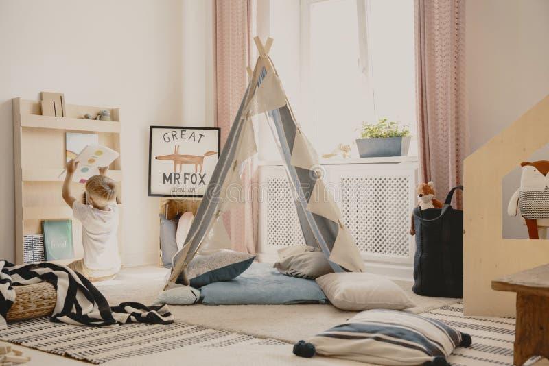 枕头和地毯在唯一孩子,真正的照片舒适游戏室地板上  库存照片