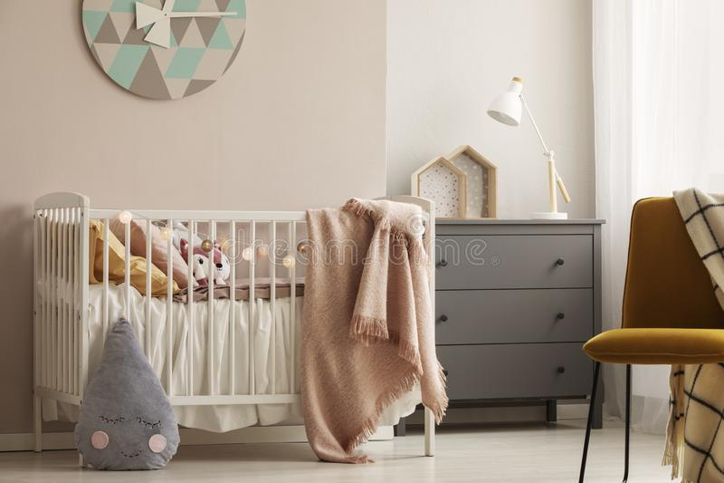 枕头和玩具在白色木小儿床有粉红彩笔毯子的在明亮的托儿所 库存图片