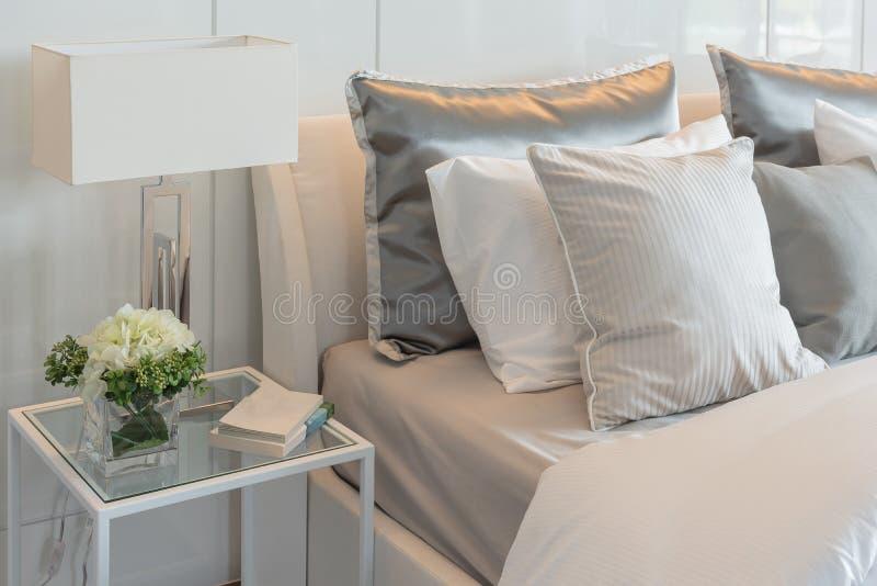枕头在与花瓶的床上设置了花在豪华卧室 免版税库存图片