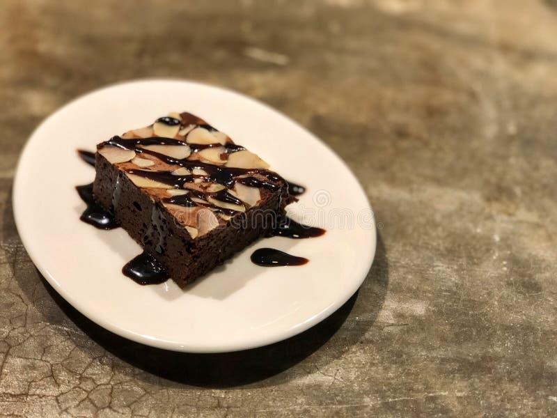 果仁巧克力冠上了用在白色盘的巧克力在水泥背景 免版税库存照片