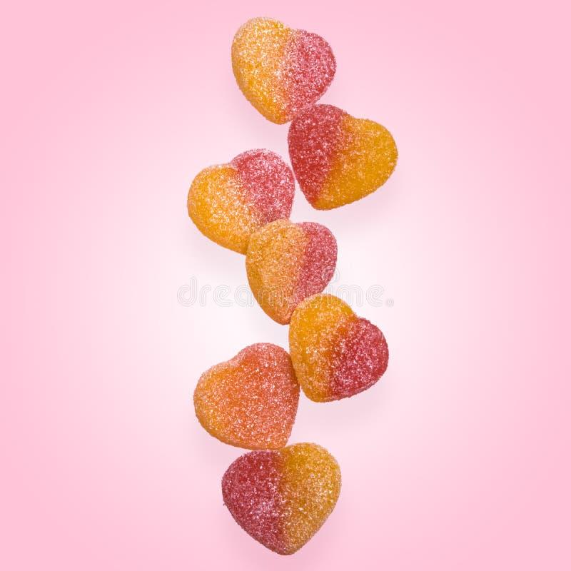 果冻飞行在天空中 以心脏的形式果冻糖果在桃红色 库存图片