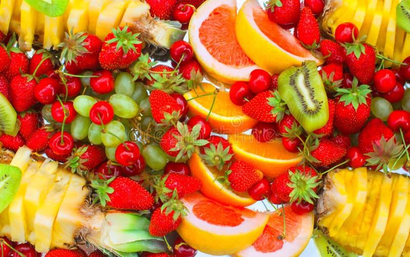 果子切了桔子、香蕉、猕猴桃、樱桃、葡萄柚、说谎在一块白色板材的草莓、葡萄和菠萝 免版税库存照片