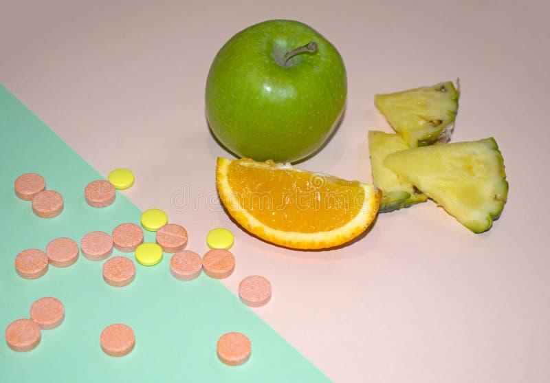 果子和药片在蓝色和桃红色背景 健康和自然维生素 库存图片