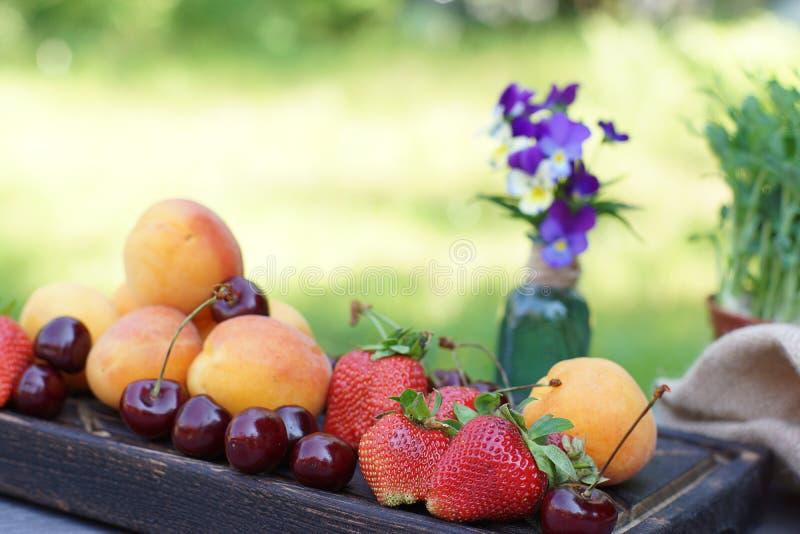 果子和莓果在一张桌上的一个木板说谎本质上,在瓶子的花束旁边 免版税图库摄影