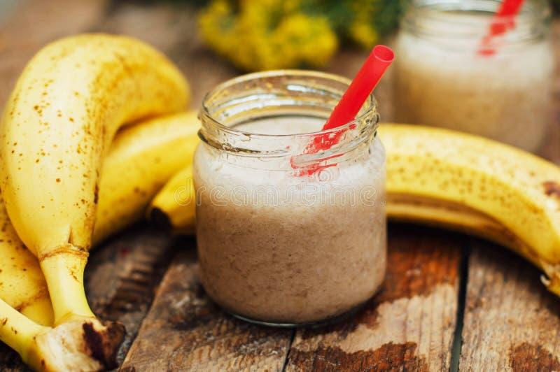 果子圆滑的人 香蕉圆滑的人用牛奶 在一张木桌上的香蕉圆滑的人 健康早餐:香蕉圆滑的人用燕麦粥 B 免版税库存照片