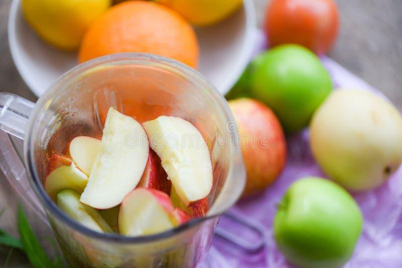果子在准备健康汁液夏天成份的搅拌器的圆滑的人/新鲜水果切片 免版税库存图片