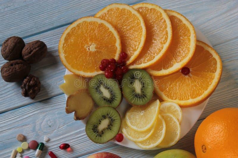 果子在板材猕猴桃、桔子、石榴和药片说谎 免版税库存照片