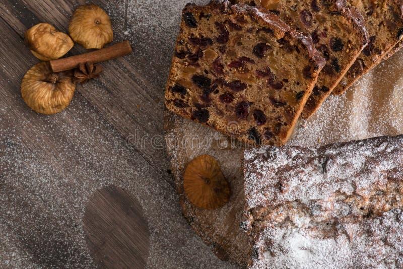 果子在黑褐色木桌上的Cristmas蛋糕 桂香、八角和无花果 免版税库存照片