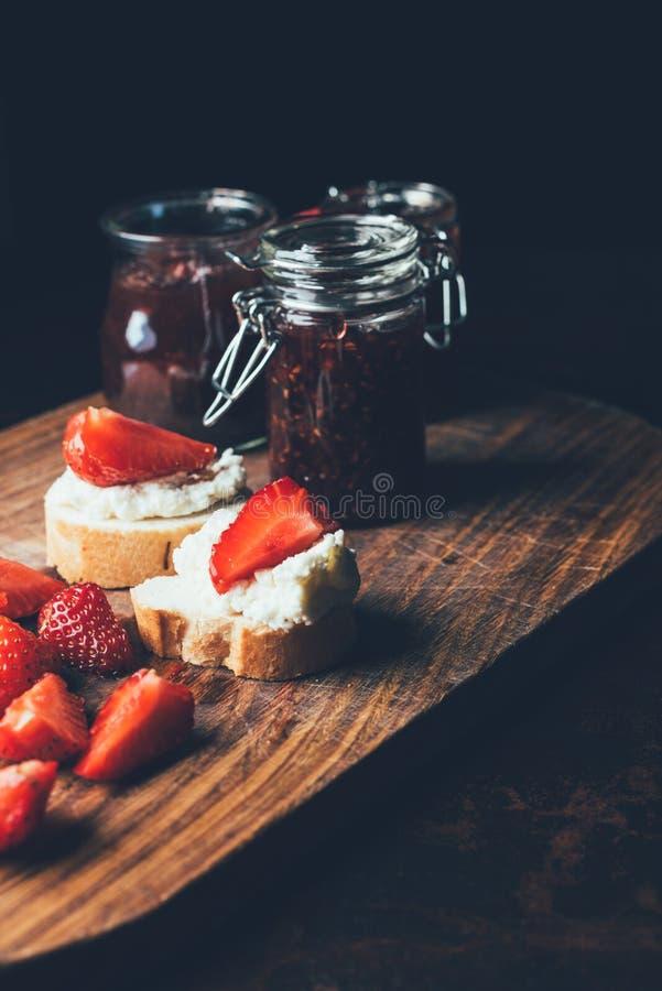 果子果酱选择聚焦用不同的瓶子,三明治用乳脂干酪,草莓切片和果子在切板阻塞 图库摄影