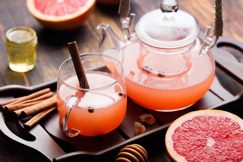 果子清凉茶用香料和蜂蜜在玻璃茶壶和杯子黑暗的木背景中 免版税库存图片